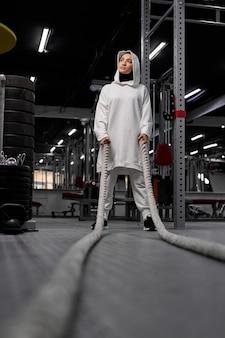 Mulher muçulmana cansada faz uma pausa durante os exercícios de crossfit usando corda. jovem mulher bonita no hijab esportivo fica para descansar. na academia