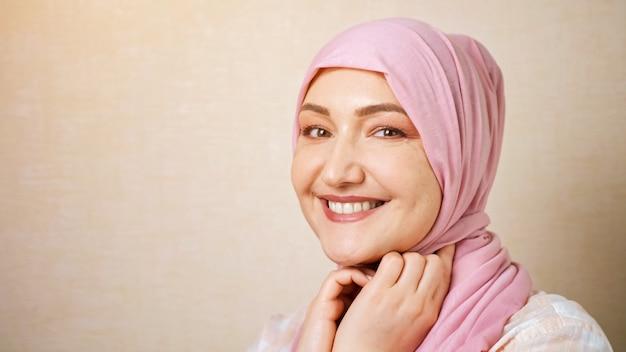 Mulher muçulmana caucasiana com um lenço na cabeça rosa sorrindo, olhando para a câmera