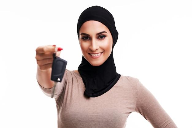 Mulher muçulmana com as chaves do carro sobre o branco