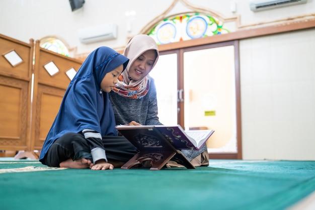 Mulher muçulmana com crianças lendo o alcorão juntos