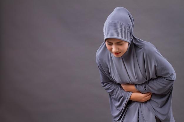 Mulher muçulmana com dor de estômago, cólica menstrual, dor abdominal, intoxicação alimentar