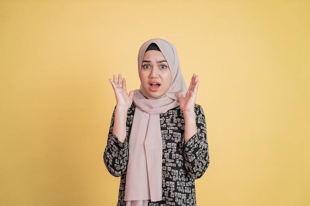 Mulher muçulmana com expressão facial confusa e gesto chocado