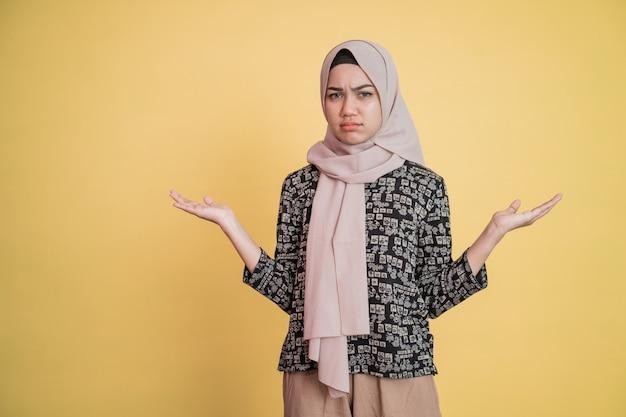 Mulher muçulmana com expressão facial taciturna e gesto de mão lateral desamparado