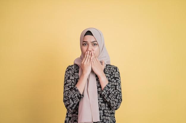Mulher muçulmana com gesto de expressão facial em choque cobrindo a boca