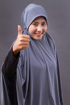 Mulher muçulmana com hijab apontando o polegar para cima