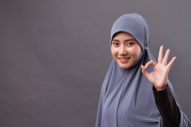 Mulher muçulmana com hijab apontando para cima em sinal de ok