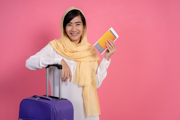 Mulher muçulmana com passaporte e cartão de embarque, segurando a mala
