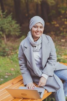 Mulher muçulmana com seu laptop no parque