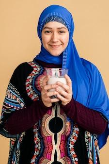 Mulher muçulmana com um copo de leite de soja