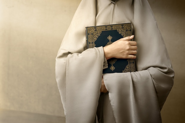 Mulher muçulmana com um véu de pé e segurando o alcorão com fundo de parede cinza