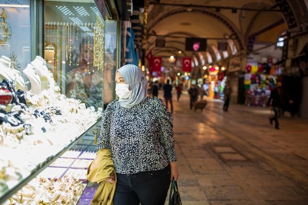Mulher muçulmana com uma máscara no bazar da turquia durante a pandemia de covid-19