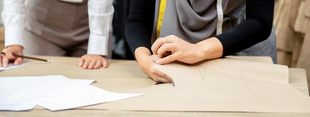 Mulher muçulmana costureira corte padrão de roupas na mesa na loja de alfaiate