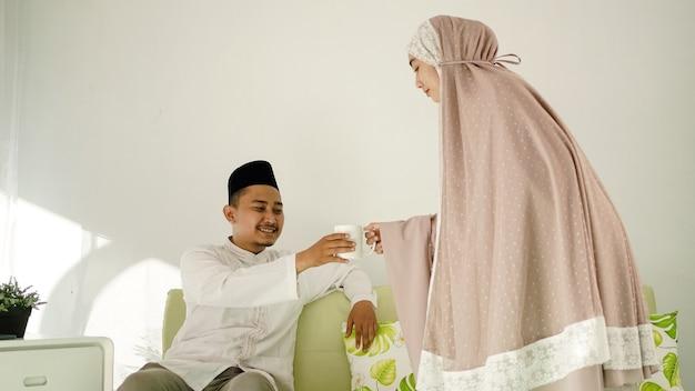 Mulher muçulmana dando um copo de bebida ao marido