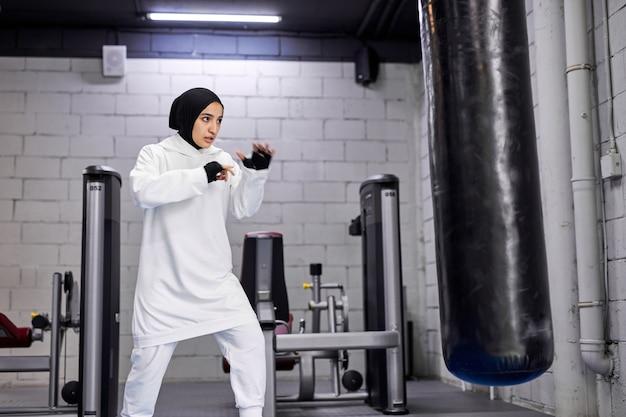 Mulher muçulmana de aptidão treinando com saco de pancadas, batendo e lutando. jovem árabe com hijab esportivo branco na academia