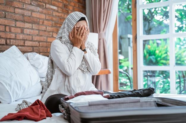 Mulher muçulmana de estresse, embalando as coisas dela