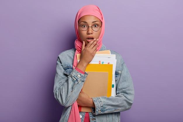 Mulher muçulmana de pele escura entorpecida e emotiva usando hijab abre a boca de espanto, segura alguns papéis e blocos de notas