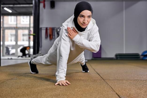 Mulher muçulmana desportiva fazendo flexões, mulher de fitness malhando exercícios de prancha. mulher motivada em hijab gosta de treinar no chão na academia
