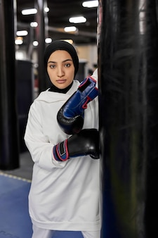 Mulher muçulmana do atleta de boxe no hijab branco ou desgaste do esporte islâmico em pé por um saco de pancadas, ajuste árabe feminino em luvas de boxe, olhando para a câmera com cara séria. indoor na academia