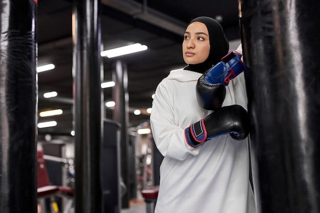 Mulher muçulmana do atleta de boxe no hijab branco ou desgaste do esporte islâmico em pé por um saco de pancadas, ajuste árabe feminino em luvas de boxe olhando para o lado com cara séria. indoor na academia