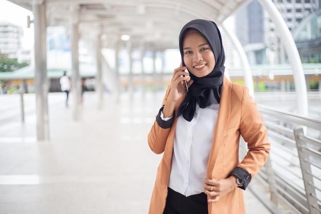 Mulher muçulmana do negócio que usa o telefone na cidade.