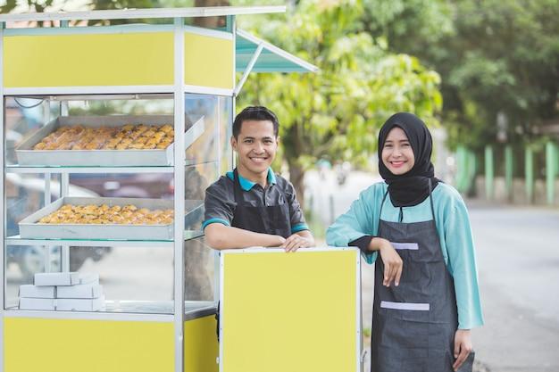 Mulher muçulmana e homem pequeno empresário e sua barraca de comida