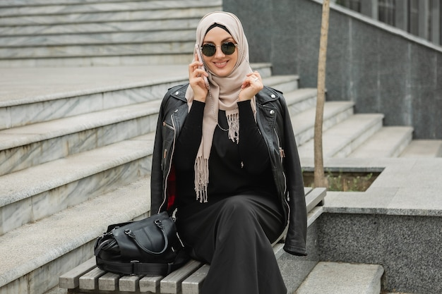Mulher muçulmana elegante e moderna em hijab, jaqueta de couro e abaya preta andando na rua da cidade falando em smartphone