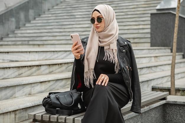 Mulher muçulmana elegante e moderna em hijab, jaqueta de couro e abaya preta andando na rua da cidade usando smartphone