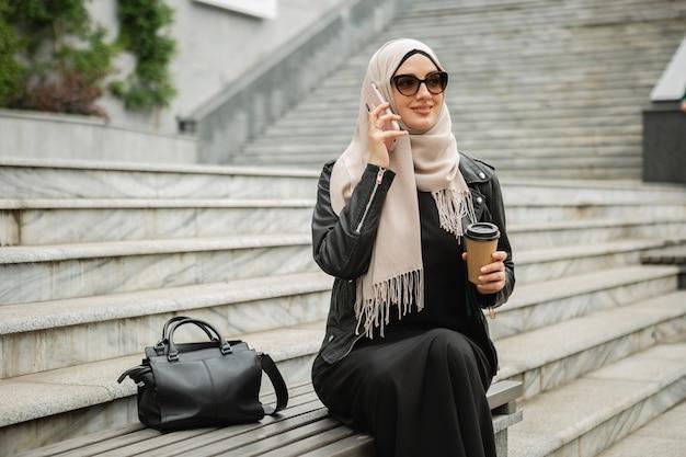Mulher muçulmana elegante e moderna em hijab, jaqueta de couro e abaya preta sentada na rua da cidade falando no celular com óculos de sol