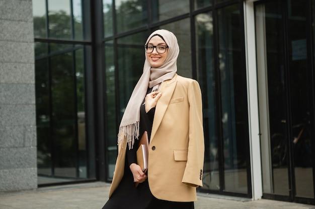 Mulher muçulmana elegante e moderna em hijab, jaqueta estilo empresarial e abaya preta andando na rua da cidade com laptop