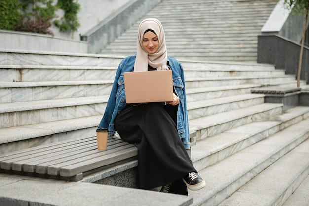 Mulher muçulmana elegante e moderna em hijab, jaqueta jeans e abaya preta sentada na rua da cidade trabalhando em um laptop