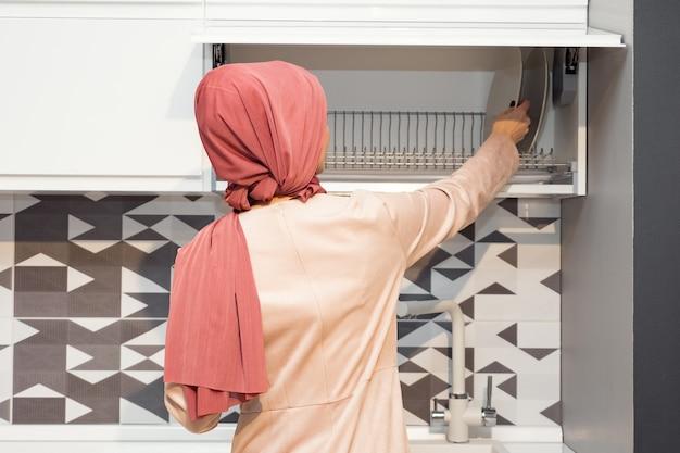 Mulher muçulmana em hijab abre armário de cozinha em cozinha moderna