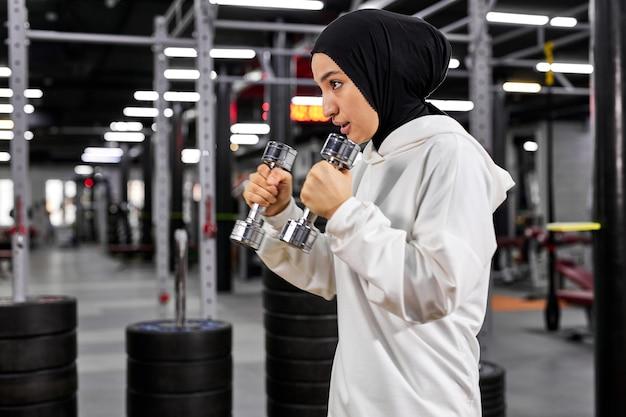 Mulher muçulmana em hijab branco, exercitando-se com halteres no ginásio, desfrutando de um estilo de vida saudável ativo, concentrado no treino, copie o espaço esporte, fitness, conceito de treinamento. vista lateral