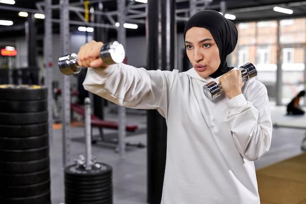 Mulher muçulmana em hijab branco, exercitando-se com halteres no ginásio, desfrutando de um estilo de vida saudável ativo, concentrado no treino, copie o espaço esporte, fitness, conceito de treinamento