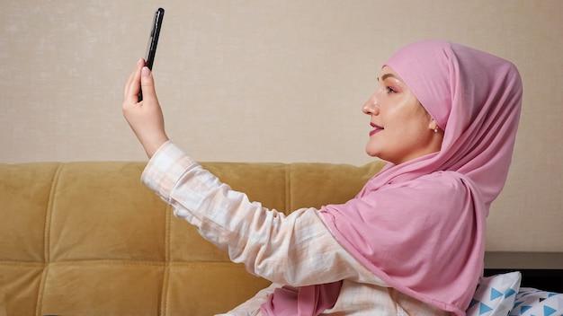 Mulher muçulmana em hijab falando por link de vídeo