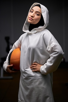 Mulher muçulmana em pé com uma bola de basquete, posando para a câmera após o treino, jovem mulher praticando esportes, usando hijab
