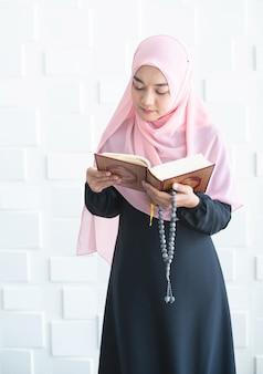 Mulher muçulmana em pé mão segure contas ler alcorão
