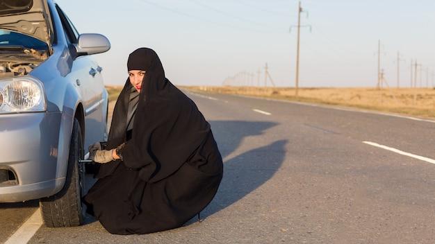 Mulher muçulmana em traje nacional troca o volante de um carro.