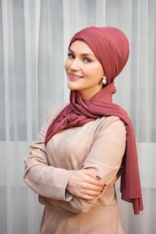 Mulher muçulmana em um lenço vermelho e roupas fechadas.