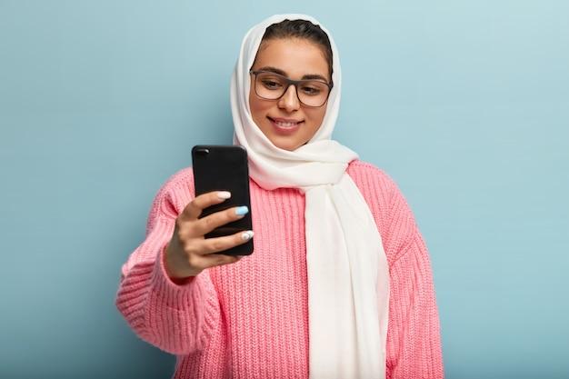 Mulher muçulmana encantada com sorriso gentil, segura celular na frente, faz selfie retrato, usa óculos retangulares óticos e véu, faz manicure. hora de fazer foto