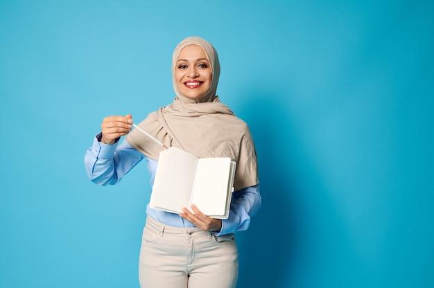 Mulher muçulmana encantadora em hijab com um lindo sorriso aponta uma caneta em uma folha de papel branca em branco diariamente. fundo azul, copie o espaço