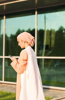 Mulher muçulmana enviando mensagens em um telefone celular na cidade