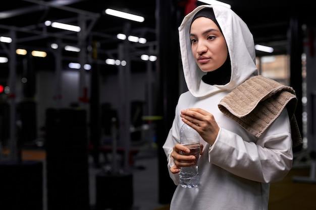 Mulher muçulmana esportiva em hijab vai tomar um gole de água durante o treino na academia, fazer uma pausa, descansar, usando hijab esportivo branco