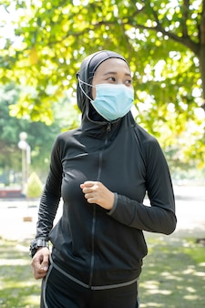 Mulher muçulmana esportiva usa máscara correndo ao ar livre no parque Foto Premium