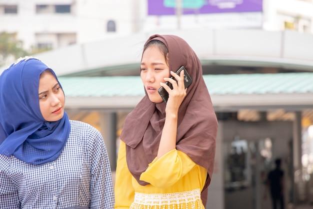 Mulher muçulmana está ao telefone enquanto sua amiga está olhando para ela