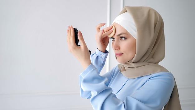 Mulher muçulmana está aplicando pó compacto, olhando para o espelho.