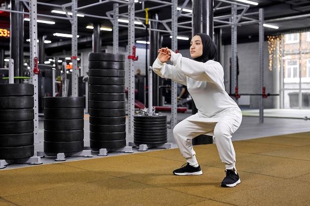 Mulher muçulmana está envolvida no esporte. mulher árabe exercitando-se no ginásio, usando o hijab esportivo branco. esporte, fitness, conceito de alongamento