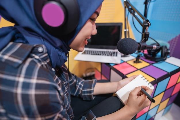 Mulher muçulmana está gravando um podcast no estúdio com um laptop e fazendo anotações com uma caneta