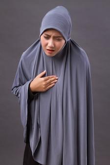 Mulher muçulmana estressada e doente com refluxo ácido, sintomas de gerd