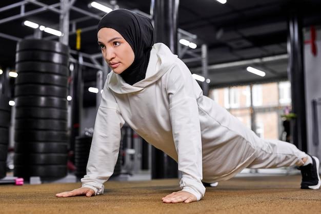 Mulher muçulmana faz flexões. mulher árabe atlética forte e em forma que executa sozinha no moderno centro de fitness treino de treino, conceito de esporte