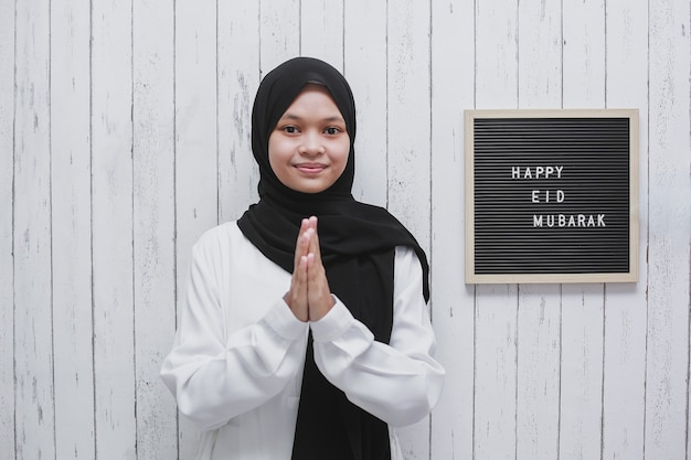 Mulher muçulmana fazendo uma pose de saudação como um símbolo de perdão com um quadro de correio dizendo feliz eid mubarak na parede